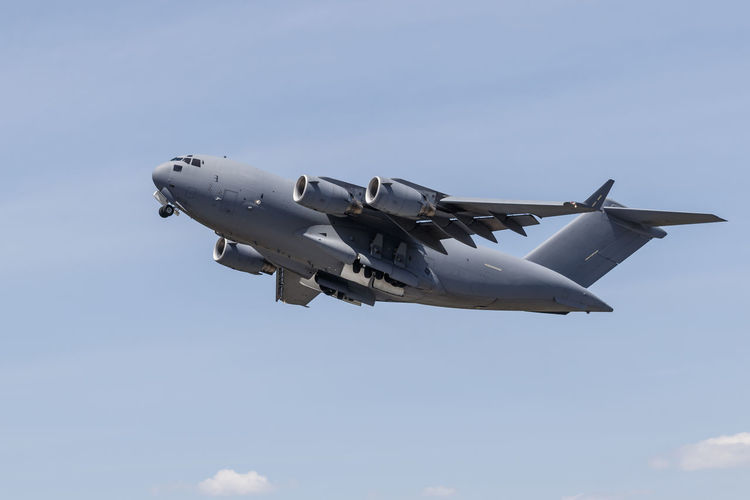 A C-17 Globemaster III heavy transport aircraft Air Vehicle Aircraft Airplane Blue C-17 Cloud Cloud - Sky Day Flying Globemaster Healthy Eating Low Angle View Mid-air Military Mode Of Transport No People Outdoors Part Of Sky Transportation White