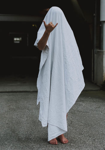 Woman gesturing while standing covered by white textile on footpath
