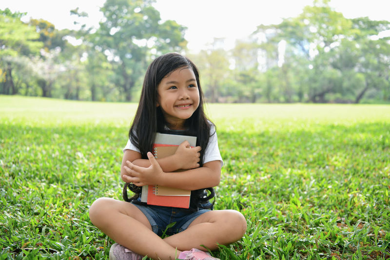 Smiling Girl With Books Looking Away While Sitting On Grassy Field At Park