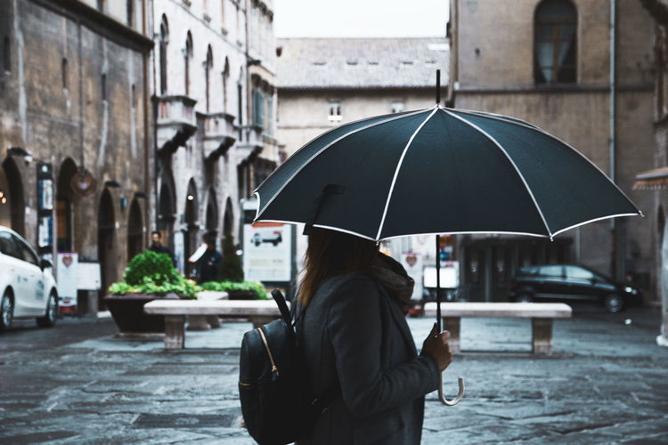 Lady WhOAdult Architecture Building Exterior Built Structure City City Life Day Focus On Foreground Lifestyles Men One Person Outdoors People Real People Rear View Street Under Water Weather Women First Eyeem Photo