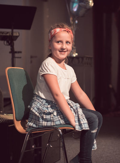 Smiling girl looking away while sitting on chair at home