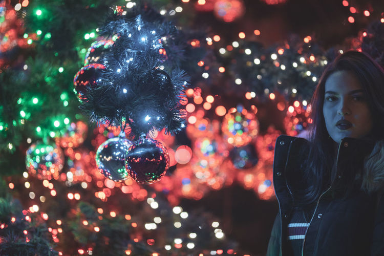 Portrait of young woman standing against illuminated christmas tree at night