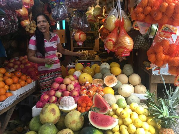 A woman sells fruits at a market in Manila. Food Stories Manila, Philippines Manila Oranges Watermelon Pineapple Lemon Fruit Orange - Fruit Market Market Stall Retail  Healthy Eating Choice Abundance Freshness Food For Sale Small Business
