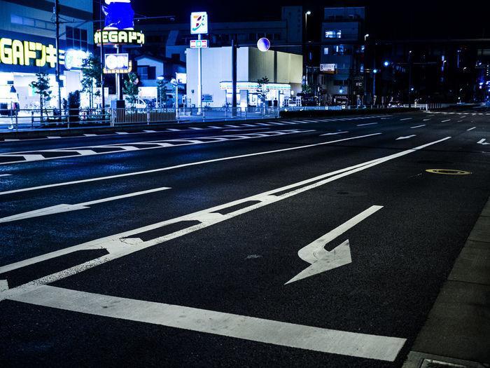 Arrow symbol on road in city at night