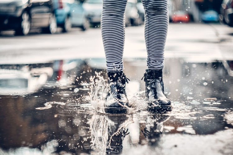 Low section of person standing on road in rain