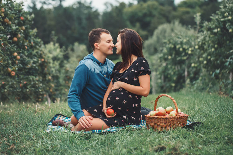 Young couple kissing in basket on field