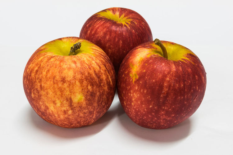Close-up of apples on table against white background