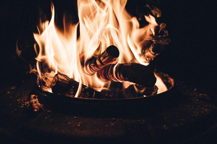 Close-up of bonfire on log at night