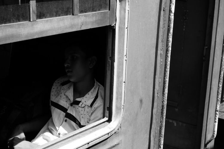 Young man sitting in train seen through window