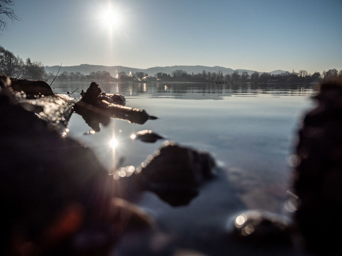 Water Sky Nature Sunlight Lake Lens Flare Day Beauty In Nature Selective Focus Scenics - Nature Outdoors Mountain Sun Sunny Focus On Background Solid Tranquility Rock Reflection Surface Level Bright