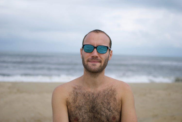 Man wearing sunglasses standing at beach against sky