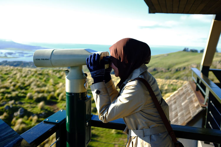 Side View Of Woman Looking Through Coin-Operated Binoculars Against Sky