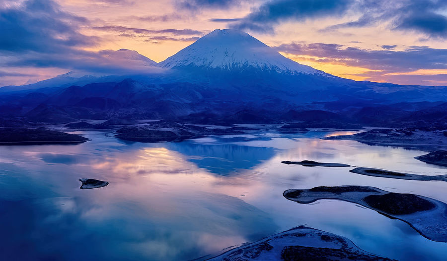 Aerial view of lake by snowcapped mountains against sky during sunset