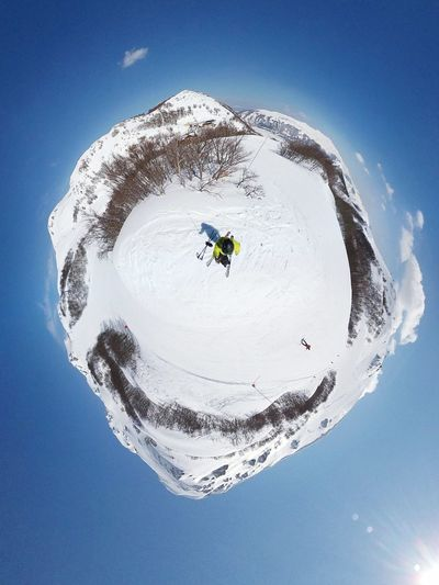 Little planet format of man on snowcapped mountain against sky