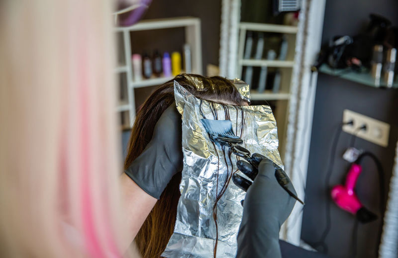 Cropped image of hairdresser dying customer hair at salon