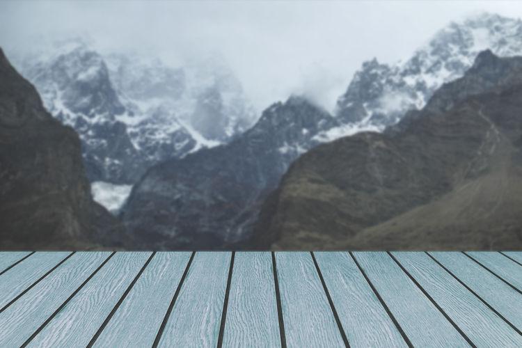 Blue wooden planks against misty snow capped karakoram mountain range in hunza valley, pakistan.