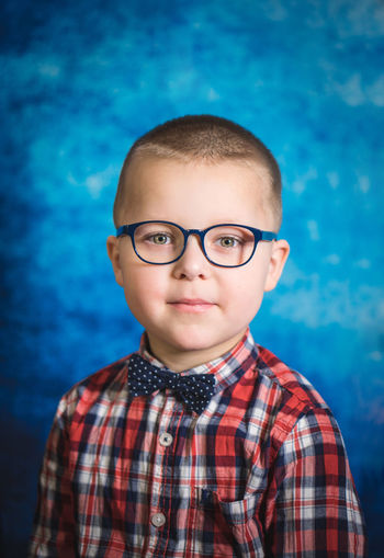 Portrait of boy wearing eyeglasses against blue background