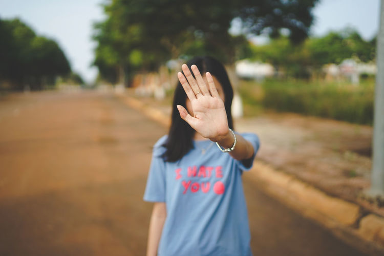 Young Woman Covering Face With Hand While Standing On Road
