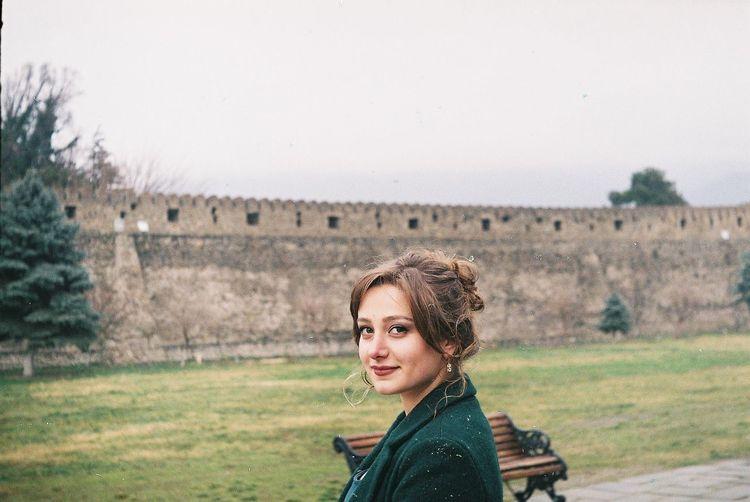 Portrait of smiling beautiful woman against castle