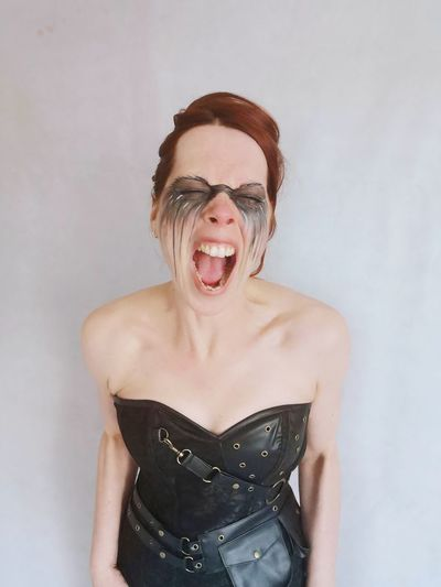 Young woman with face paint shouting while standing against white background