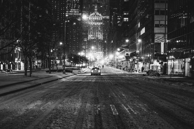 Snow Covered Road In City At Night