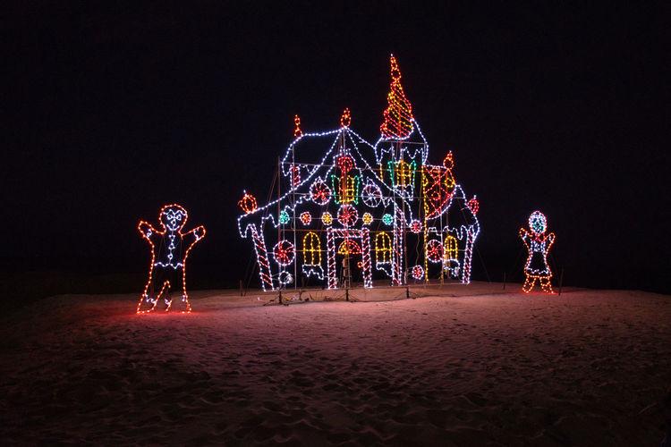 Illuminated christmas lights at amusement park ride at night