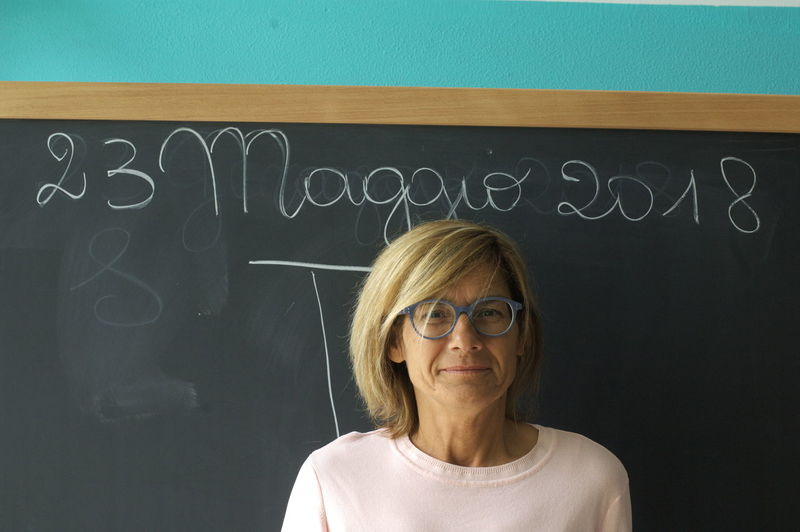 Portrait Of Smiling Teacher Standing Against Blackboard In Classroom