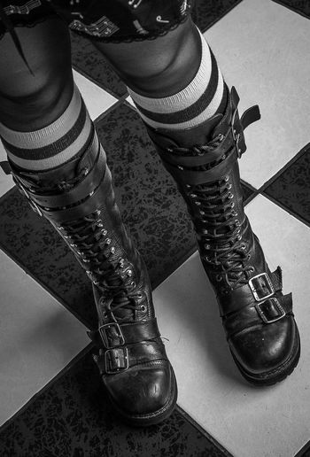 Female leather cothurnus in checkered floor with black and white pattern Close-up Fashion Gothic Gothic Style Human Body Part Human Leg Lifestyles One Person One Woman Only Pattern People Shoe Women