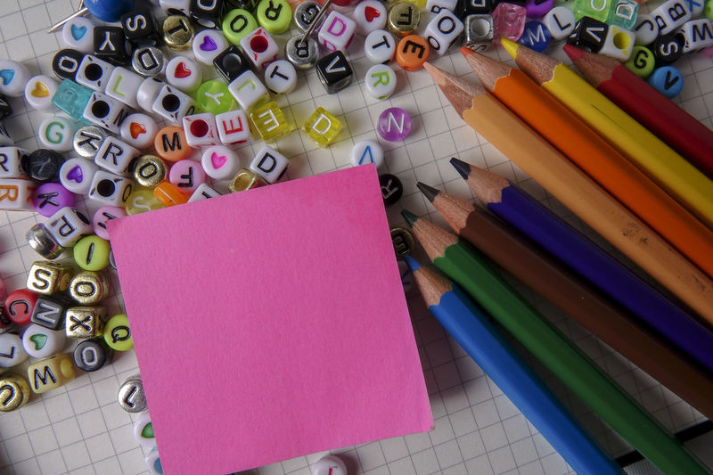 EDUCATIONAL CONCEPT WITH POST IT STICKER; COPY SPACE Adhesive Note Art And Craft Blank Book Choice Close-up Colored Pencil Education High Angle View Indoors  Large Group Of Objects Multi Colored No People Note Pad Paper Pen Pencil Publication Reminder Still Life Variation Writing Instrument