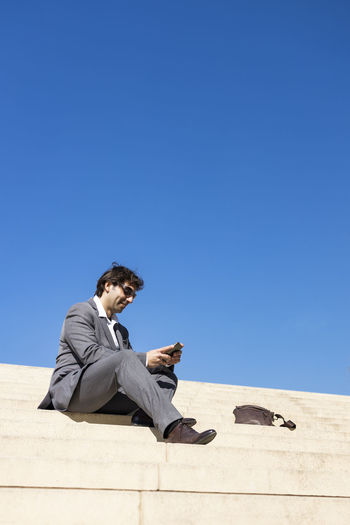 Man sitting on smart phone against clear blue sky