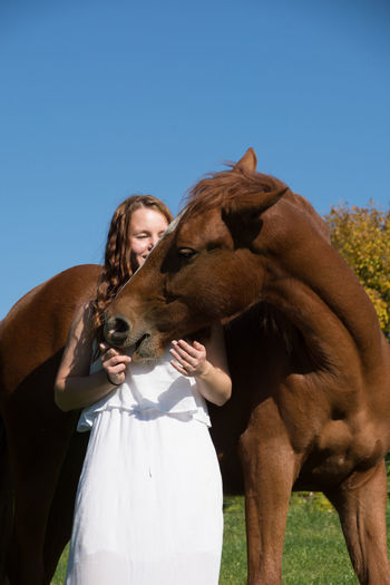 Low angle view of young woman with horse standing against clear sky