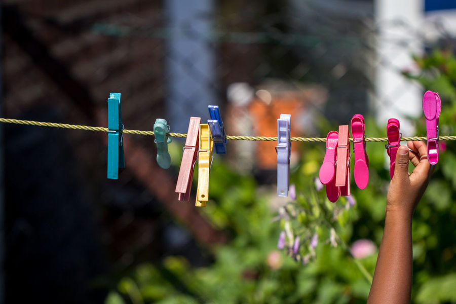 African African American City Clothes Pegs Colourful Afro Caribbean Black British Child Childhood Close-up Colorful Focus On Foreground Garden Human Body Part Human Hand Kid Laundry Pegs Lifestyles Outdoors People Person Of Color Playing Washing Line Young Person
