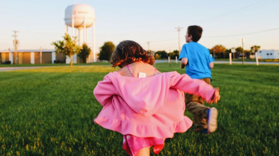 Rear view of girl with brother running on grassy field