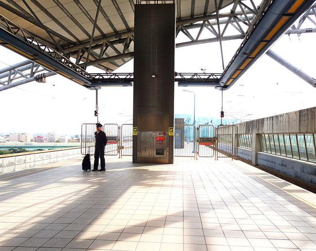 Man waiting at railroad station platform
