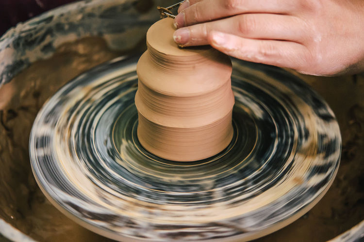 Creating ceramic products of white clay close-up. the sculptor in workshop makes clay jug closeup.