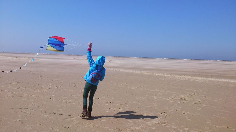 Rear view of girl flying kite at beach against clear sky