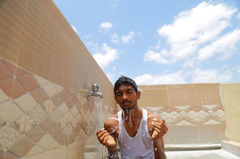 Young man splashing water on his face by faucet at terrace