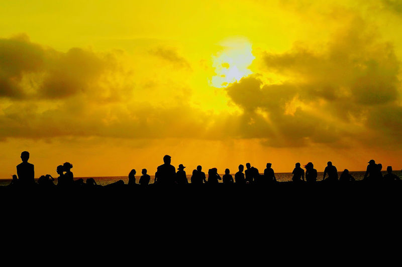 Silhouette people against orange sky during sunset