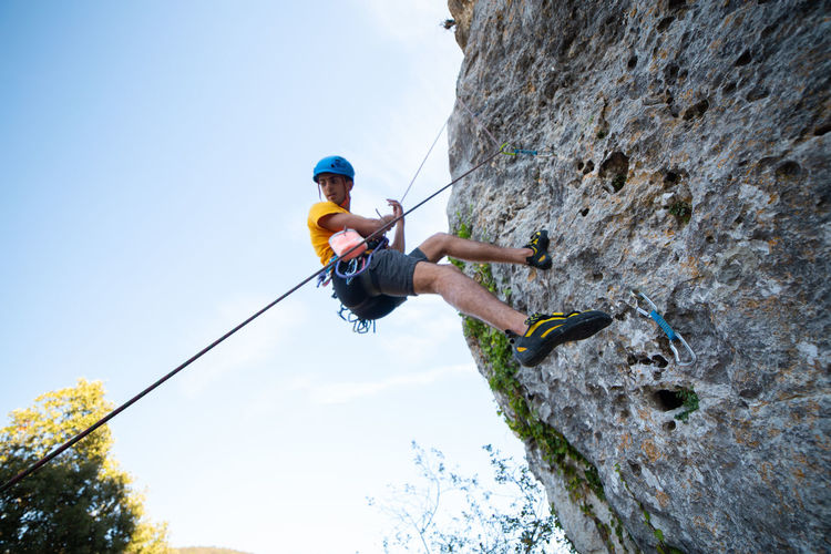 From below shot of male climber climbing mountain wall on amazing sunny day Man Climbing Rock Cliff Sunny Sky Sport Mountain Extreme Close-up Activity Height Rope Challenge Strong Male Adventure RISK Exercise Grip Young Storm Cloud Stone Athlete Dificult Moving