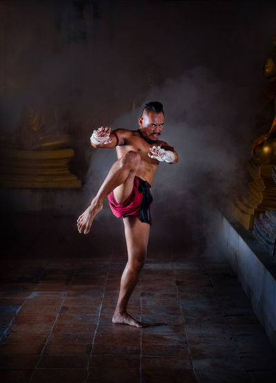 Portrait Of Shirtless Mid Adult Man Practicing Muay Thai At Night