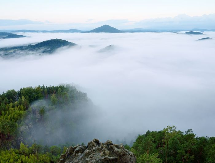 Scenic view of misty mountains against moody sky