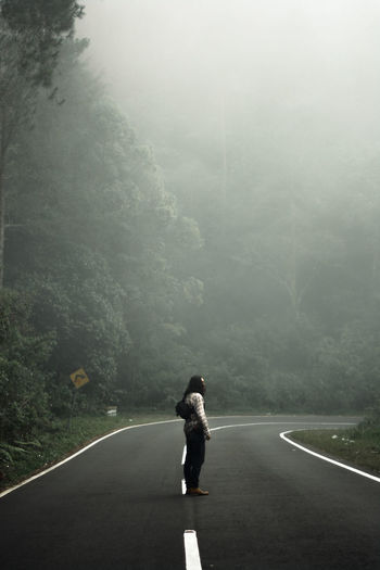 Side view of man standing on road