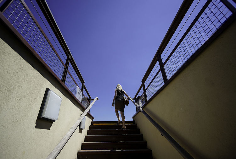 Rear View Of Woman Moving Up Stairs Against Clear Blue Sky
