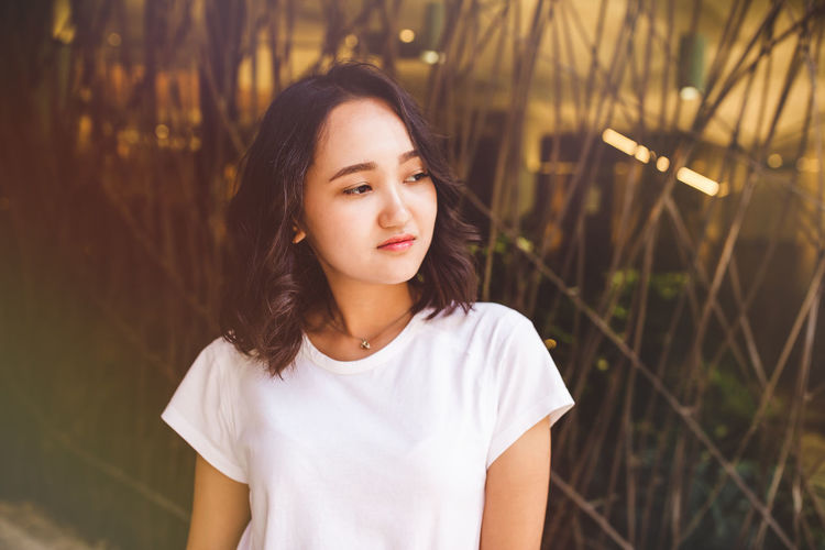 Young asian woman in a white t-shirt calm looking at the side. street portrait, lifestyle concept