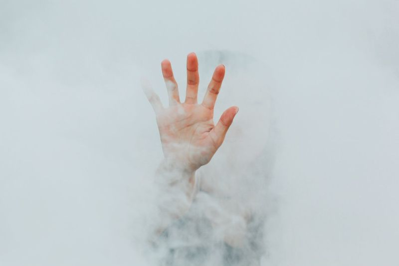 Hand Of Person Amidst White Smoke