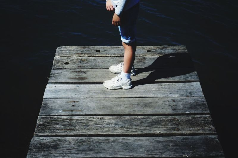 Low section of man standing on pier over lake