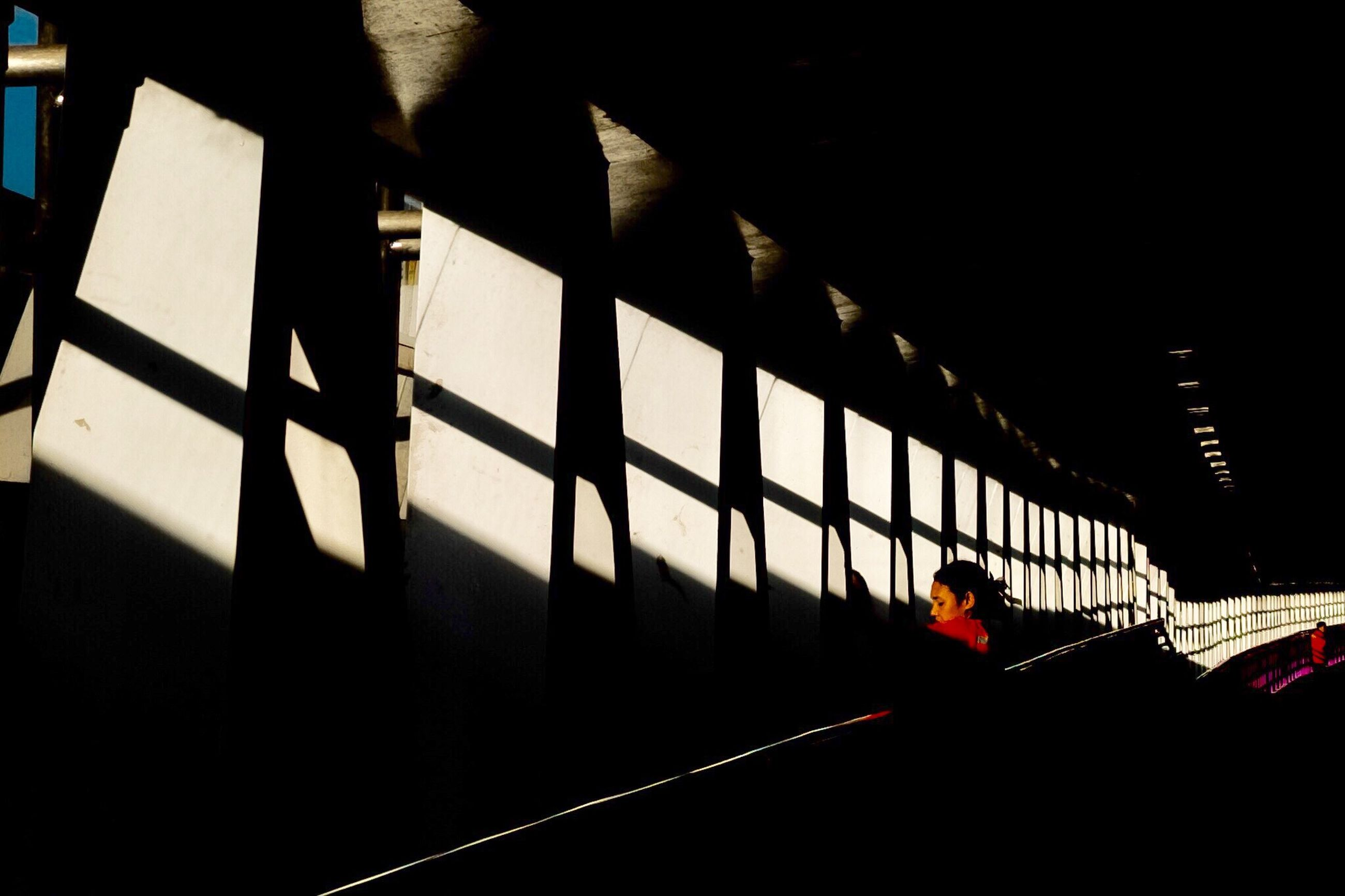 silhouette, indoors, real people, built structure, sunlight, architecture, shadow, transportation, one person, standing, day, men, women, illuminated, people