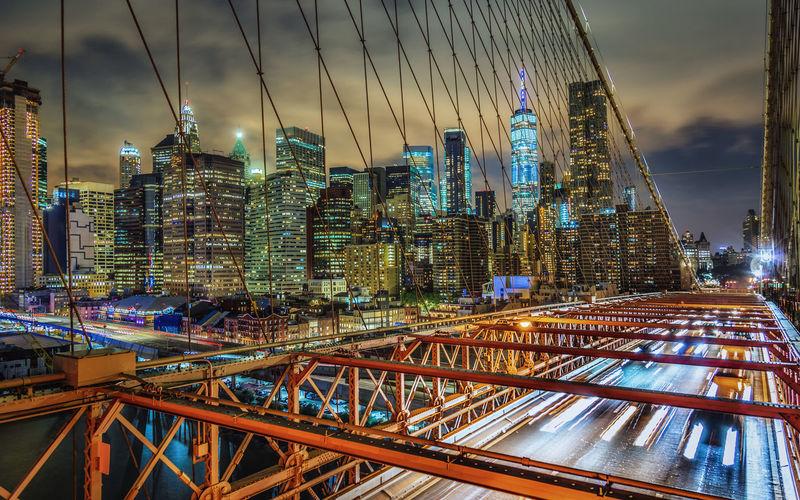 Bridge against modern buildings in city at night