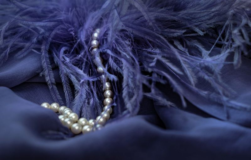 Close-Up Of Pearl Necklace On Blue Fabric
