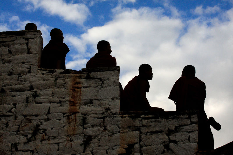 Low angle view of silhouette people standing against cloudy sky